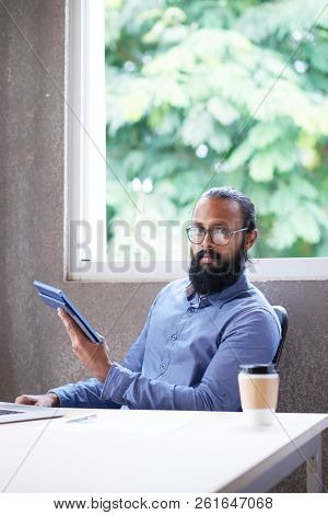 Portrait Of Confident Bearded Manager Working With Touchpad In Office