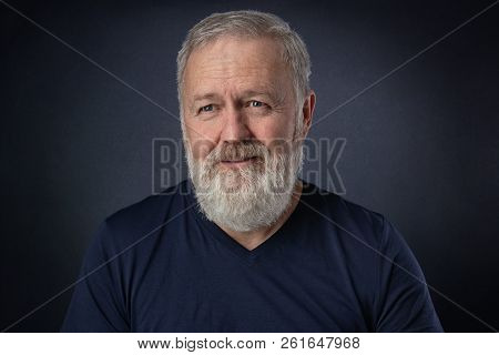Happy 60 Year Old Man With Gray Beard Posing In The Studio