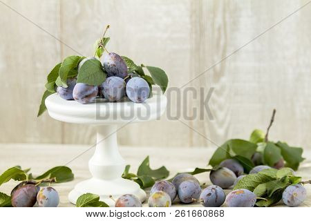 Many Juicy Beautiful Amazing Nice Plums On Light Wooden Background. Beautiful Food Art Background