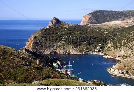 Sea port city by the sea. Yachts on the pier in the blue sea. White boats and yachts in the port city against the backdrop of green mountains. Balaclava in the Crimea. poster