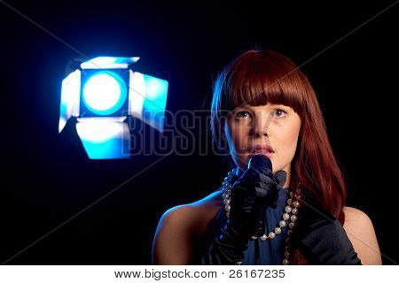 young female singer holds microphone, blue stage light at background, isolated on black