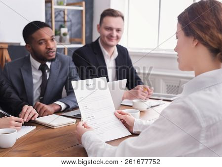 Female Employer Holding Applicant Resume During Office Interview