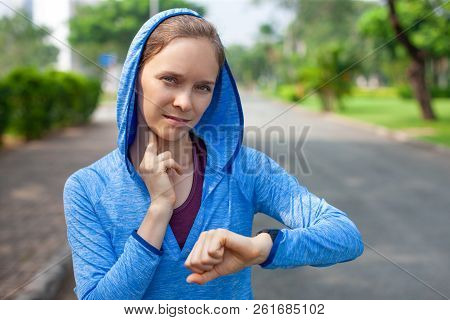 Confident Young Female Athlete Checking Pulse With Smartwatch. Portrait Of Caucasian Woman Taking Pu