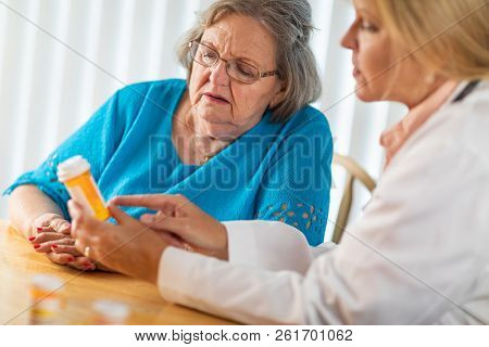 Female Doctor Talking with Senior Adult Woman About Medicine Prescription.