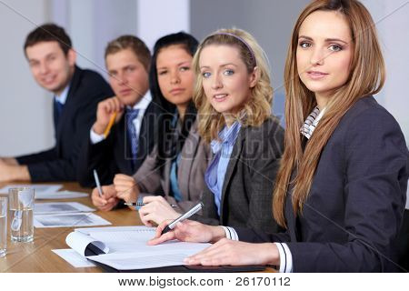 Young attractive businesswoman sitting at conference table with 4 more people, working on some paperwork