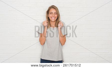 Beautiful young woman over white brick wall excited for success with arms raised celebrating victory smiling. Winner concept.