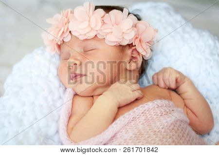Cute And Adorable Newborn Caucasian Girl Smiling In Her Sleep. Pink Head Band With Flowers And A Lig