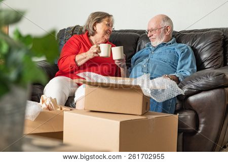 Tired Senior Adult Couple Resting on Couch with Cups of Coffee Surrounded with Moving Boxes.