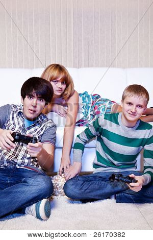Friends playing computer game and eating popcorn