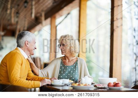 Happy beautiful senior wife with curly hair wearing glasses touching shoulder of husband and supporting him while they talking at breakfast on porch