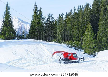 Winter Activity In The Mountains With A Red Snow Groomer Surrounded By Snow And Green Fir Forest In