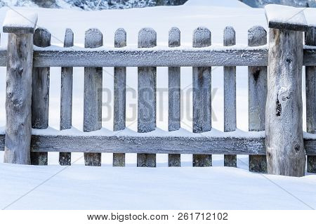 Winter At Countryside With A Snowy Old Wooden Fence, Surrounded By A Thick Layer Of Snow, On A Sunny