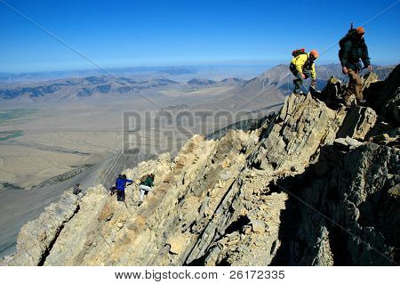 Several people climbing along rocky ridge on a trail
