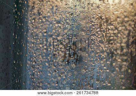 Window Screen Behind Glass With Rain Dropd