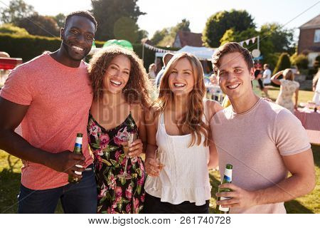 Portrait Of Friends Enjoying Drinks At Summer Garden Fete