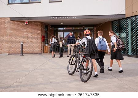 Group Of High School Students Wearing Uniform Arriving At School Walking Or Riding Bikes Being Greeted By Teacher