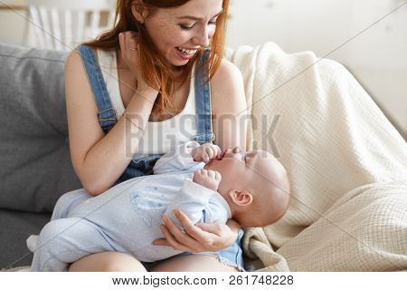 Sweet Intimate Moment Between Charming Beautiful Young Red Haired Mother And Chubby Infant: Cheerful
