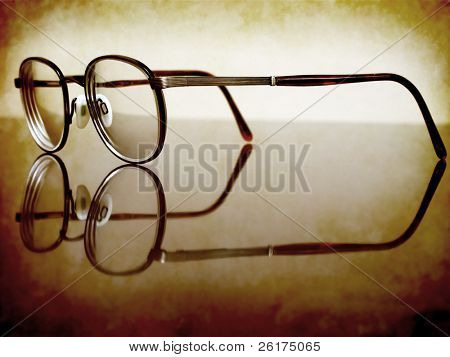 Closeup of Antique Eyeglasses on desk with reflection
