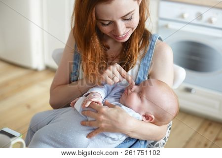 Indoor Shot Of Happy Beautiful Young Red Haired Mom In Denim Jumpsuit Holding Sleeping Infant And Pr