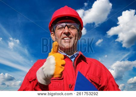 Smiling Worker Over Blue Sky And Clouds Background. Worker In Red Hard Hat And Coveralls Gesturing T
