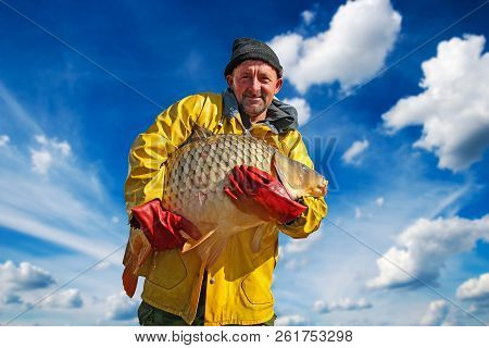 Fisherman Holding A Big Fish Against Blue Sky And Clouds. Portrait Of Smiling Fisherman With Big Car