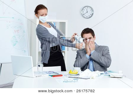Image of businessman sneezing while his partner in mask offering him to put on one in office