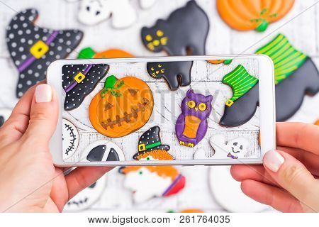Woman Taking Photo Of Halloween Gingerbread Cookies On Mobile Phone. Trendy Instagram Photo Shot. Co