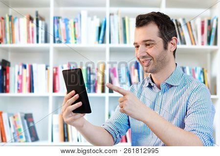Man Relaxing And Reading Ebook On Bookshelf Background