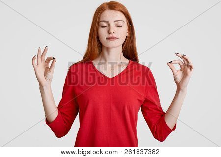 Calm Red Haired Freckled Woman Meditates In Studio, Makes Okay Gesture With Both Hands, Dressed In R