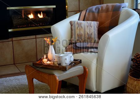 Hygge Home Comfort With Soft Leather Bucket Chair, Candles, Blanket And Tea Beside Gas Fireplace.  H