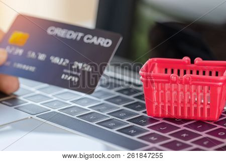 Empty Red Basket And Hand Holding Credit Card Mockup On Laptop Keyboard. Consumer Can Buy Product An