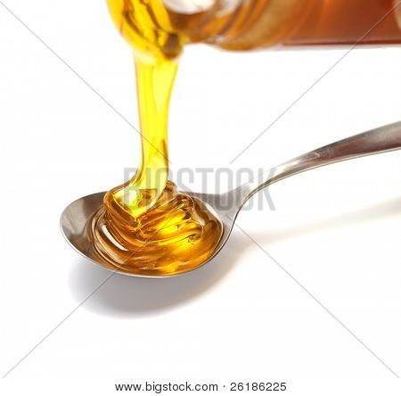 honey pouring into spoon  isolated  on white background