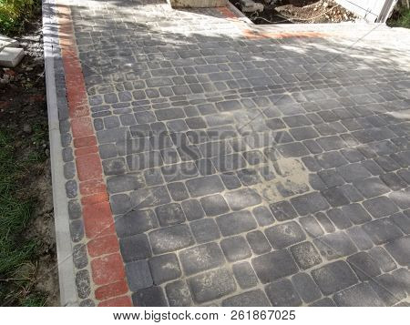 Newly Laid Gray And Red Pavement Tiles Edged With Curbs In The Yard. The Concept Of Beautification O