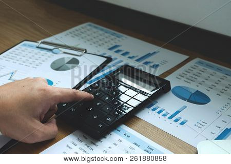 Businessmen Calculate The Income From The Export Business On The Wood Table.business Concept.