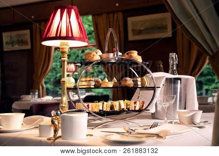 Vintage Late Afternoon Tea Stand With Sandwiches, Cakes And Tea As See Through The Window Of A Train
