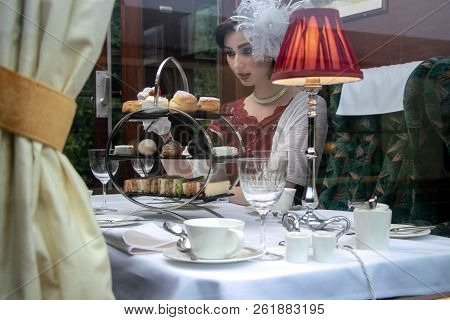 Beautiful Woman In Vintage Clothing Enjoying Afternoon Tea In Train Carriage