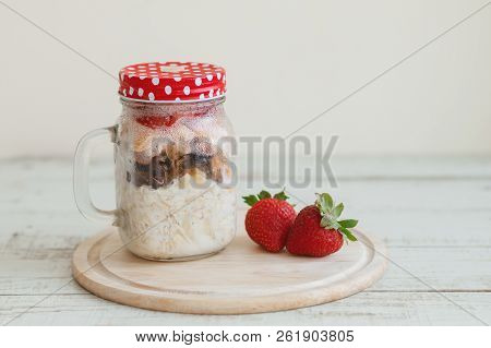 Overnight Oats In A Glass Jar And Fresh Strawberry On Wooden Board. Easy Breakfast Recipe