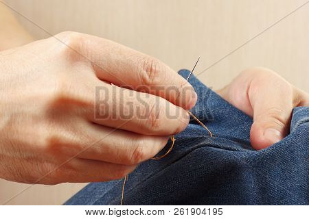 Hands Of Clothier Sew Denim Fabric With A Needle Close Up