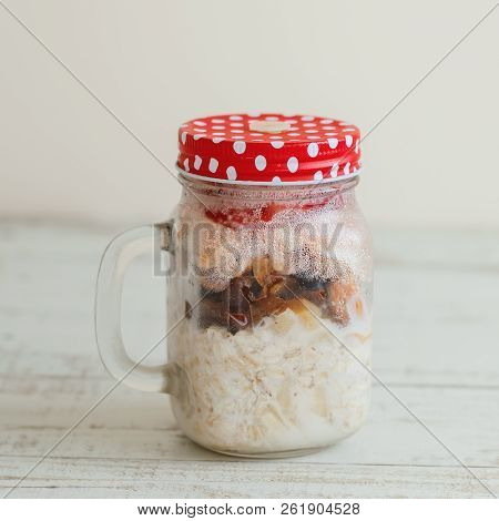 Overnight Oats With Milk, Dried Fruits, Berries And Nuts In A Tall Glass Jar Served On Wooden Table,