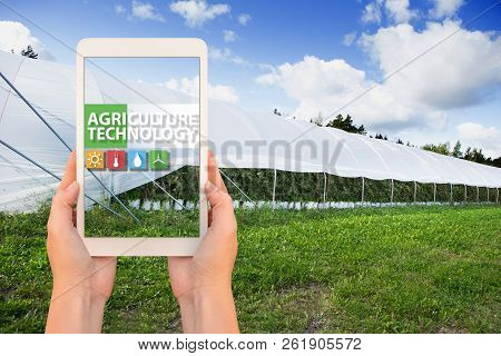 A Farmer Holding A Tablet On The Background Of The Greenhouse. On The Screen, The Inscription