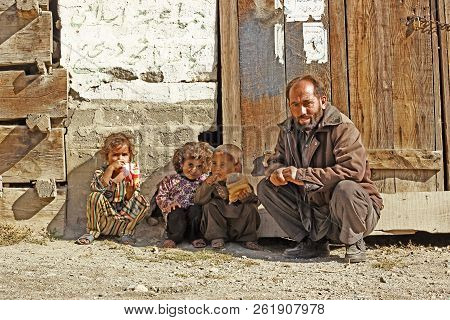 Man Sitting With His Kids And Smiling In Swat District, Khyber Pakhtunkhwa, Pakistan 14/10/2015