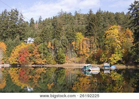 autumn color and houseboats, reflected in a calm ocean