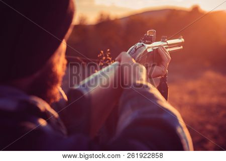 Close Up Snipers Carbine At The Outdoor Hunting. Rifle Hunter Silhouetted In Beautiful Sunset. Autum