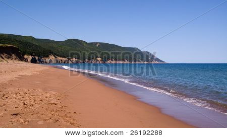 Orange sand beach, waves and highlands against clear blue summer sky; Cape Breton, NS, Canada