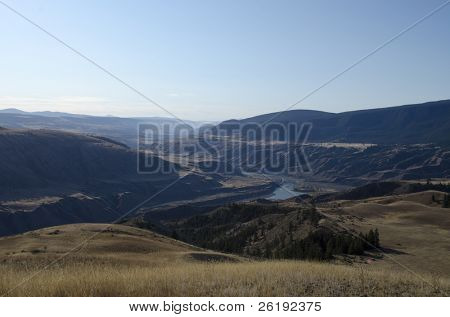 Alpine vistas with view over grasslands, valley and forest, under a blue sky