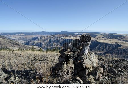 Alpine vistas with view over grasslands, valley and forest with stump and cairn in foreground