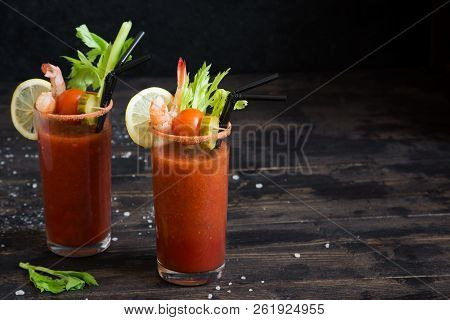 Bloody Mary Cocktail In Glasses With Garnishes. Tomato Bloody Mary Spicy Drink On Dark Wooden Backgr