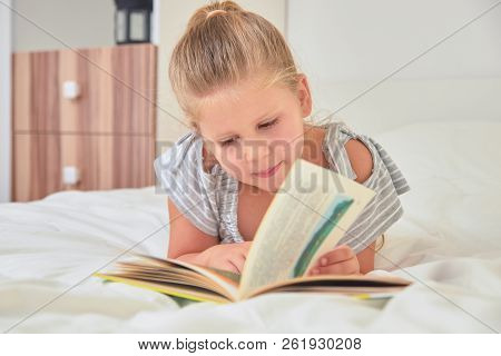 Little Blonde Girl Reading Storybook While Lying On Bed In Her Room