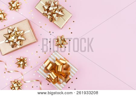 Fashion Gifts Or Presents Boxes With Golden Bows And Star Confetti On Pink Pastel Table Top View. Fl
