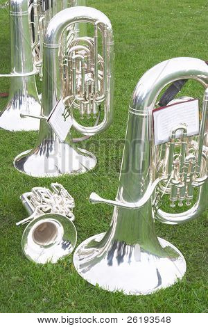 Tubas and a cornet or trumpet on the grass as a brass band takes a break during a village fair. poster